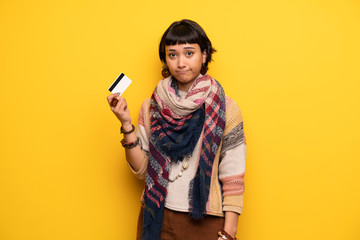 Young hippie woman over yellow wall  holding a credit card