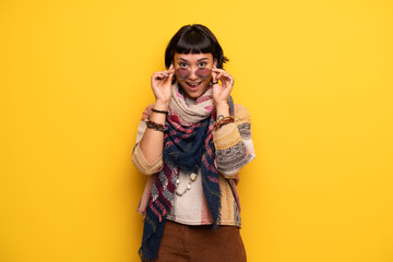 Young hippie woman over yellow wall with glasses and surprised