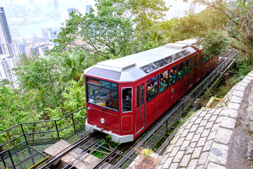 Victoria Peak Tram and unidentified people with Hong Kong city skyline background. landmark and destination for tourist attractions in HK