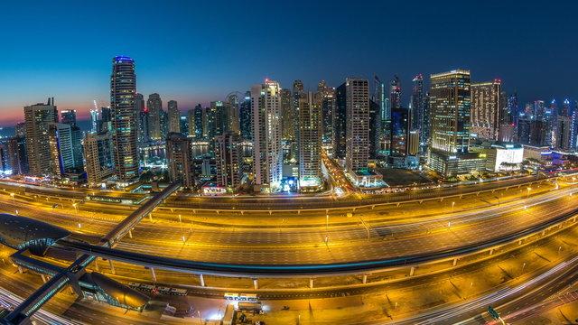 Dubai marina with traffic on sheikh zayed road panorama day to night timelapse lights turn on.