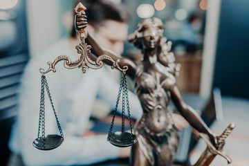 scales of justice. a young man is a lawyer, a judge, a prosecutor. concept of jurisprudence