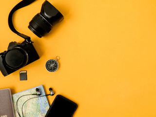 top view travel concept with camera, map, passport and travel accessories on yellow background, Tourist essentials, vintage tone effect