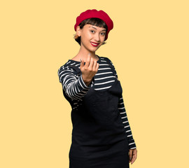 Young woman with beret inviting to come with hand. Happy that you came over yellow background