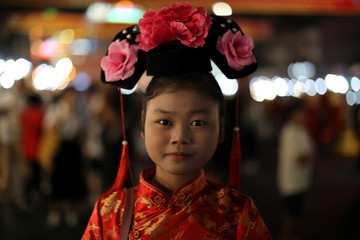A girl wears traditional Chinese clothes during the celebrations of the Chinese Lunar New Year in Chinatown in Bangkok