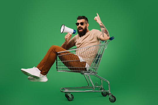 bearded man with megaphone pointing up while sitting in shopping cart isolated on green