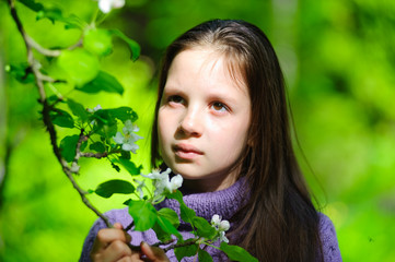 cute girl child brunette and branch blooming wild apple in spring