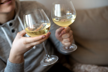 close up of hands with two white wine glasses
