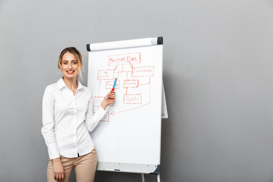 Image of smiling businesswoman in formal wear standing and making presentation using flipchart in the office, isolated over gray background