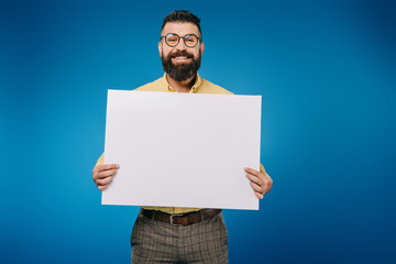 cheerful man holding blank placard isolated on blue