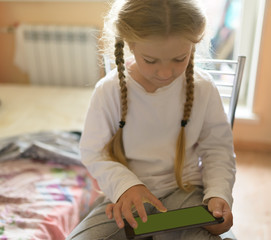 Girl playing with tablet pc. Selective focus on eyes.
