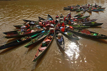 Vendors at a floating market make circle of their boats, as they perform to attract clients at Martapura river in South Kalimantan