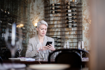 Businesswoman using smartphone in a restaurant