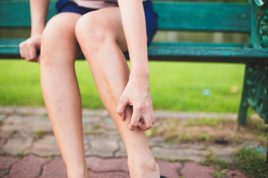 Women with his feet, itching on the lawn caused by insect bites and stings/health and medical view and devising concepts.