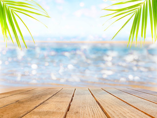 Empty surface of a wooden table on a background of beach and palm leaves.