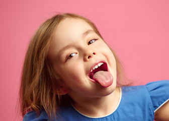 Close up shot of little girl with her tongue out over pink isolated.