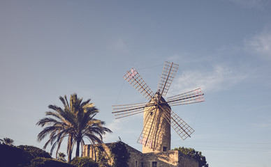 Retro toned picture of an old windmill at sunset, Mallorca, Spain.