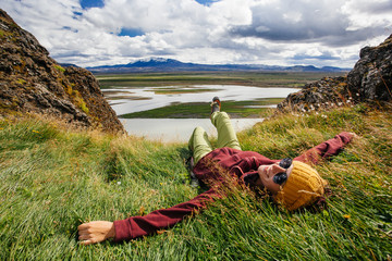 Happy young woman in bright clothes traveling Iceland, enjouing nature Wall mural