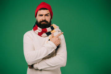 sick bearded man in hat and scarf pointing aside isolated on green