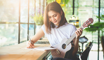 Female composer is writing music in a joyful feeling using ukulele as a device in the Vintage-style Café, Soft tone vintage style.