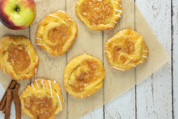 apple danish on parchment paper with apple and cinnamon sticks from above on white wood rustic background