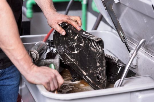 Mechanic degreasing a car engine part at service repair station .