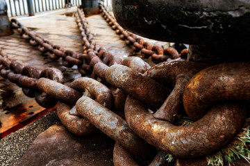 Close up of old rusty chain, industrial port with chains, crane background out of focus, sunny day, industrial concept