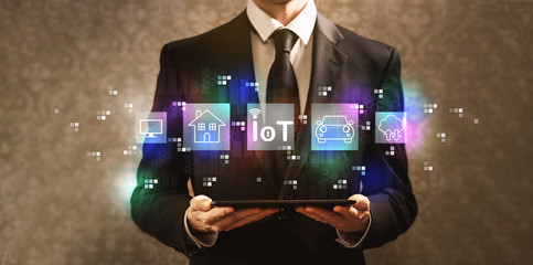 IoT theme with businessman holding a tablet computer on a dark vintage background
