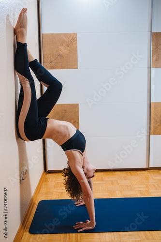 Yoga at home  Sporty beautiful young woman practicing yoga