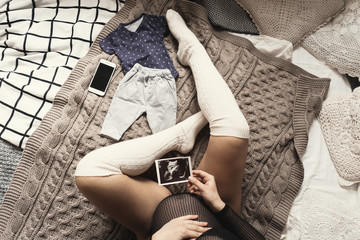 Expecting pregnant woman touching her belly while looking at ultrasound scans while relaxing on bed at home