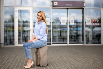 Young blonde hair business woman in shirt and denim pants standing near arrival terminal at the airport