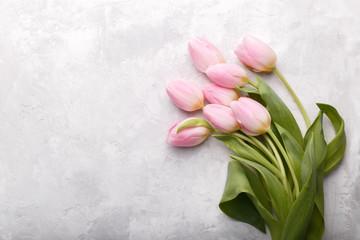 Pink tulips on grey stone background