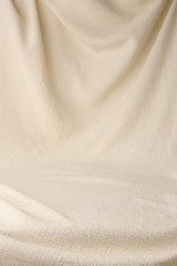 Abstract drapery cloth background. Beige woven textile drape with empty place.
