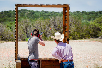 Shooting clay pigeons in Texas USA, watched by a real cowboy