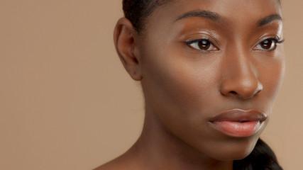 closeup portrait of mixed race black woman watching aside. Ideal skin, natural makeup, shiny glossy eyelids