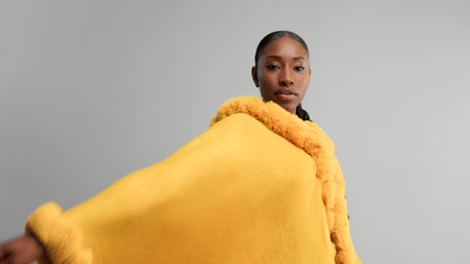 black moxed race woman in bright yellow outwear poncho on grey dancing and rolling