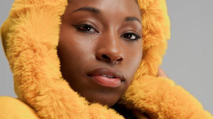 closeup portrait of black woman wears yellow hood with faux fur