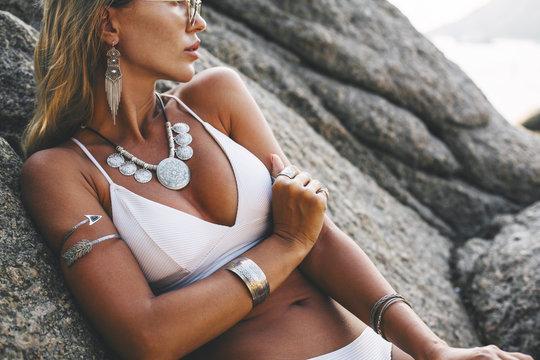 Model in white bikini and wearing boho jewellery