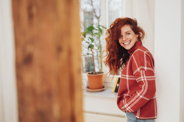 Friendly young redhead woman relaxing at home