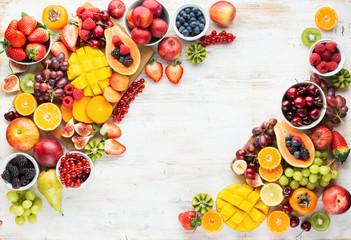 Wall Mural - Healthy raw fruits background, cut mango papaya, strawberries raspberries oranges plums apples kiwis grapes blueberries cherries, on white table, copy space, top view, selective focus