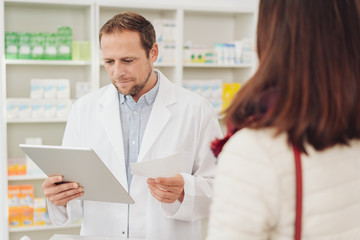 Pharmacist checking a script for a patient