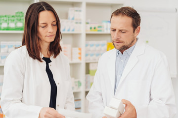 Two concerned pharmacists discussing a script