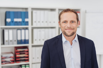 Portrait of modestly smiling adult man in office