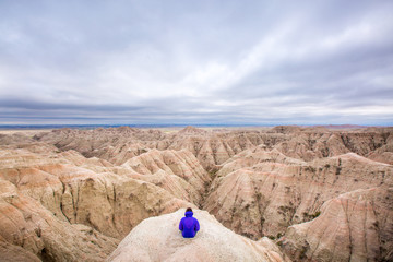 A woman looks out over the beautiful streaked hills of Badlands National Park on a stormy day. Shot from the White River Valley Overlook.