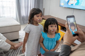 two cute girls with face painting taken picture together with smartphone