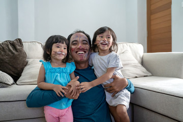 dad and his two little girls looking at camera together after having their faces painted