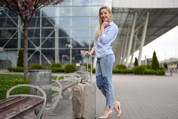 Young blonde hair business woman in shirt and denim pants standing near the terminal at the airport