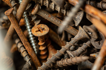 Old rusty screws and nails. Background for construction and industry. Pattern of screws and nails.