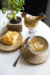 Soup with quail stands on a wooden stand and cheese pastries near the window.
