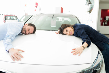 Smiling Man And Woman Hugging Their First Car
