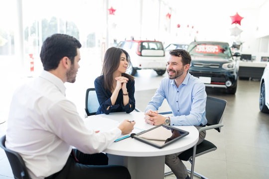 Customers And Dealer Talking About Finance In Car Salon